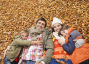 Smiling family laying in autumn leaves - CAIF02275