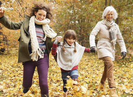 Three generations of women playing in autumn leaves - CAIF02281