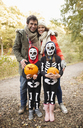 Parents smiling with children in skeleton costumes - CAIF02299