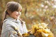 Smiling girl playing in autumn leaves - CAIF02314