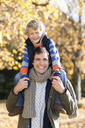 Man carrying son on shoulders in park - CAIF02323