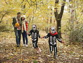 Children in skeleton costumes playing in park - CAIF02356