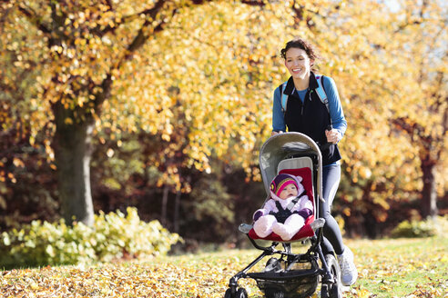 Woman running with baby stroller in park - CAIF02392