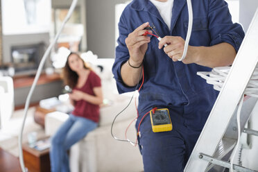 Electrician working in living room - CAIF02410