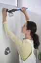 Woman working on shower head in bathroom - CAIF02419