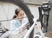 Woman working on bicycle in driveway - CAIF02425