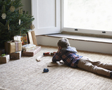 Boy playing with trains by Christmas tree - CAIF02434