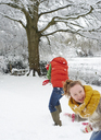 Mother and daughter playing in snow - CAIF02440
