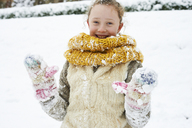 Smiling girl playing in snow - CAIF02446