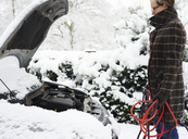 Woman working on broken down car in snow - CAIF02452