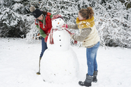 Mother and daughter making snowman - CAIF02458