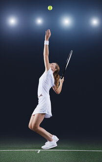 Tennis player serving ball on court - CAIF02524