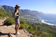 South Africa, Cape Town, woman standing looking at the coast during hiking trip to Lion's Head - ECPF00220