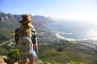 South Africa, Cape Town, woman standing looking at the coast during hiking trip to Lion's Head - ECPF00223