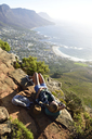 South Africa, Cape Town, woman lying on rock during hiking trip to Lion's Head - ECPF00229