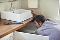 Plumber working under kitchen sink - CAIF02538