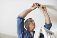 Electrician working on ceiling lights - CAIF02541