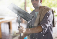 Man washing window with squeegee - CAIF02556