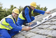 Workers installing solar panels on roof - CAIF02562