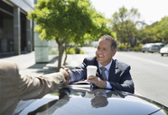 Businessmen shaking hands over car - CAIF02583