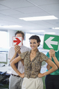 Business people holding arrows in office - CAIF02589