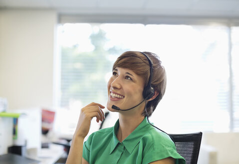 Businesswoman talking on headset at desk - CAIF02592