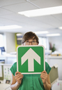 Businesswoman holding arrow sign in office - CAIF02613