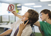 Businesswoman showing 'no cell phones' sign to colleague - CAIF02616