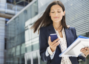 Businesswoman using cell phone in office - CAIF02637