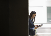 Businesswoman reading in office - CAIF02643