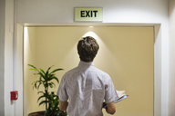 Businessman examining 'exit' sign in office - CAIF02649