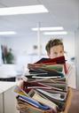 Businessman balancing folders in office - CAIF02661