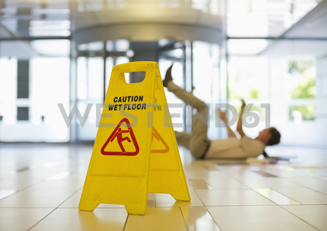 Businessman slipping on wet office floor - CAIF02664