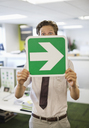 Businessman holding arrow sign in office - CAIF02667