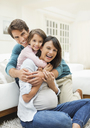 Family hugging in living room - CAIF02679