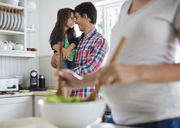 Father and daughter touching noses in kitchen - CAIF02709