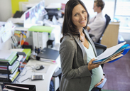 Pregnant businesswoman working in office - CAIF02715