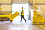 Blurred view of worker pushing boxes in warehouse - CAIF02760