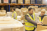Workers using laptop in warehouse - CAIF02781