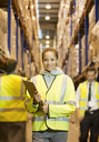 Worker holding clipboard in warehouse - CAIF02793