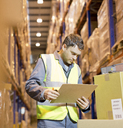 Worker reading clipboard in warehouse - CAIF02796