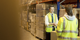 Workers talking in warehouse - CAIF02799