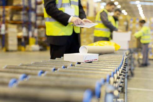 Workers checking packages on conveyor belt in warehouse - CAIF02802