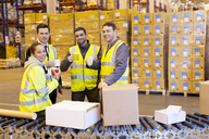 Workers drinking coffee in warehouse - CAIF02811