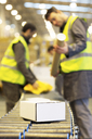 Workers checking packages on conveyor belt in warehouse - CAIF02817