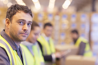 Worker standing in warehouse - CAIF02826