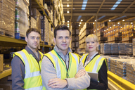 Workers smiling in warehouse - CAIF02835