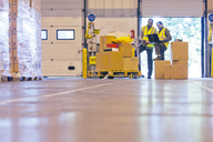 Workers checking boxes in warehouse - CAIF02838