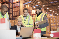 Businesswoman and workers using laptop in warehouse - CAIF02847
