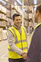 Workers shaking hands in warehouse - CAIF02850
